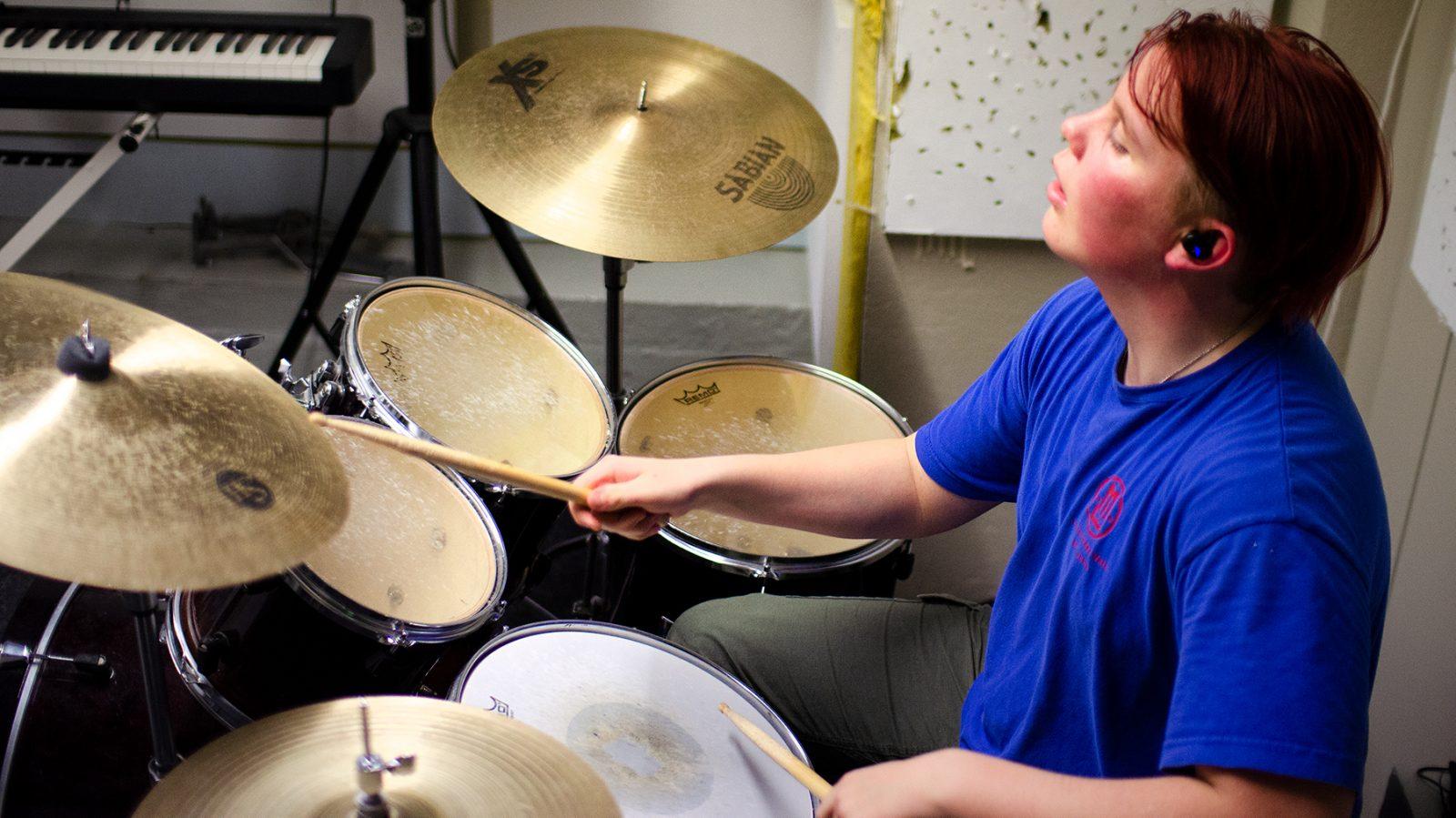 Nuori rummuttaa rumpuja.