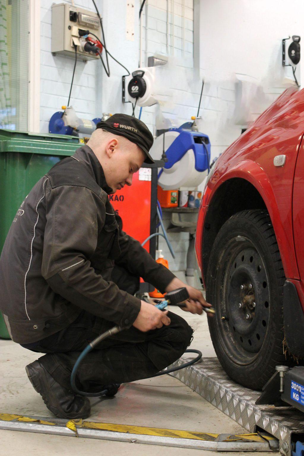 Ajoneuvoasentajaksi opiskeleva kiinnittää auton rengasta korjaushallissa.