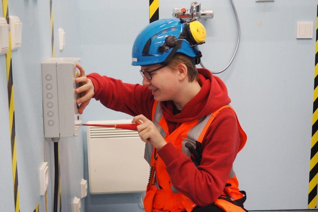 Sähköalan opiskelija ruuvaa kytkentäkaappia