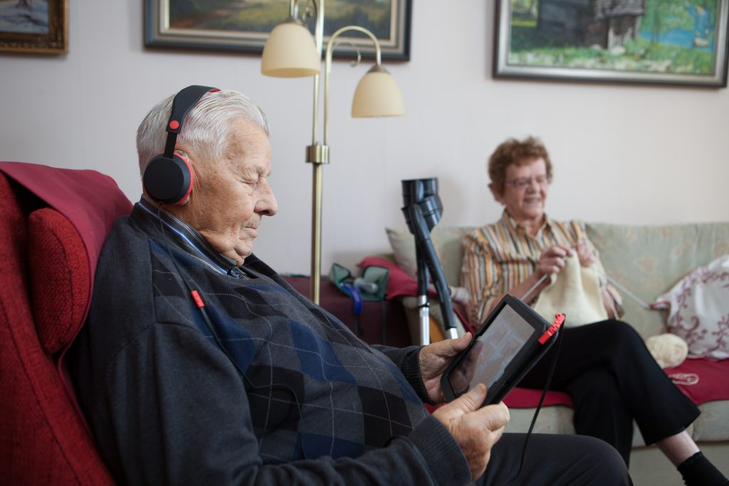 Ikääntynyt mies kuuntelee Celian äänikirjaa kuulokkeet päässä