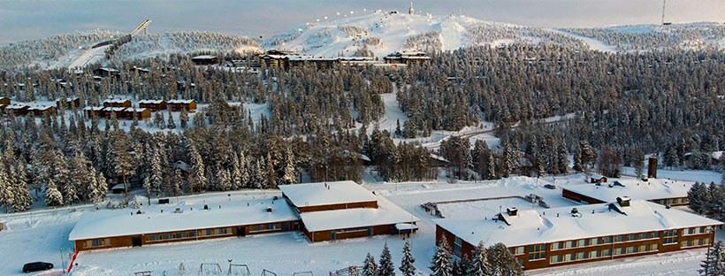 Rukan koulu sijaitsee aivan Rukatunturin juuressa. Kuvassa luminen maisema ja koulu. Taustalla hiihtohissien valot.