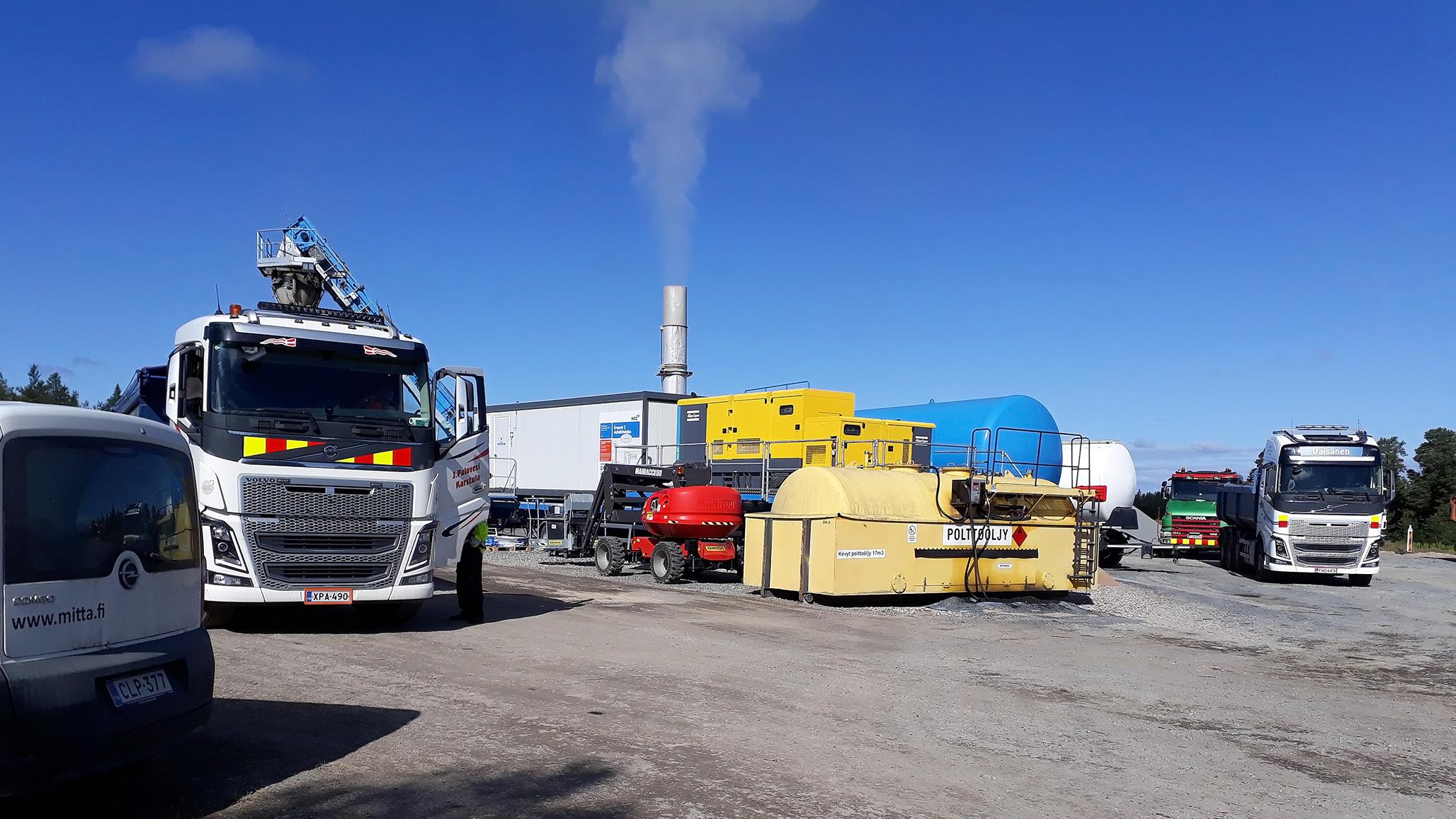 Kuorma-autoja on pysäköity öljysäiliöiden ja savuavan piipun ympärille. Taivas on sininen.