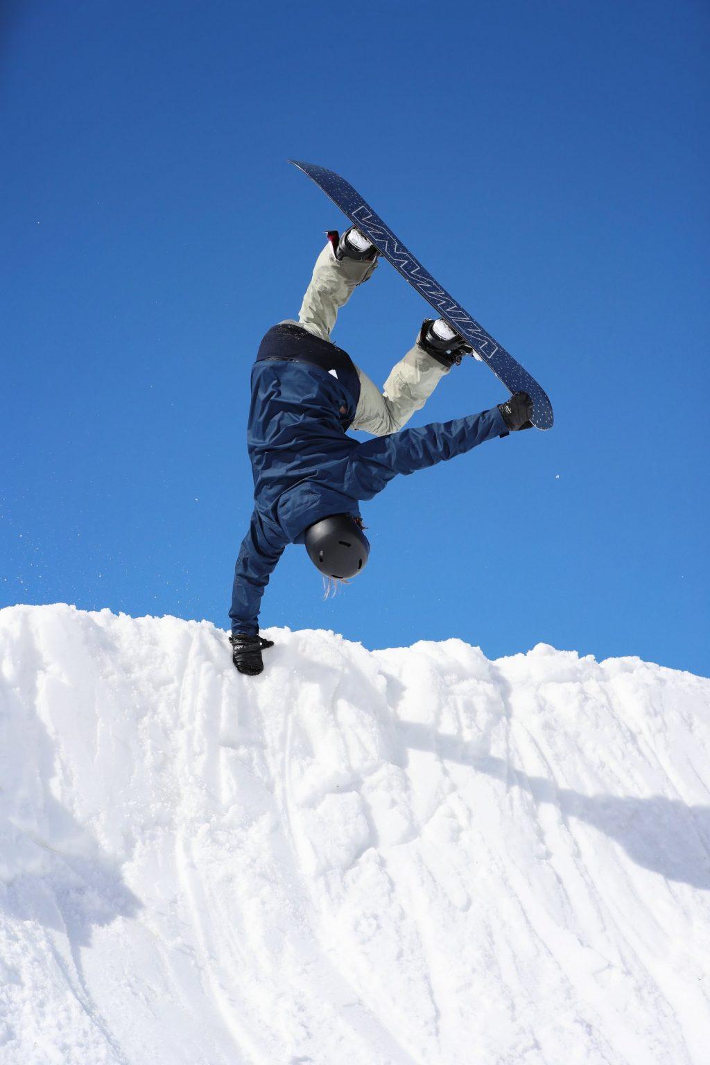 Enni Rukajärvi hyppää ja tarttuu half-pipen reunaan sekä toisella kädellään lautaansa. Taustalla on sininen taivas.