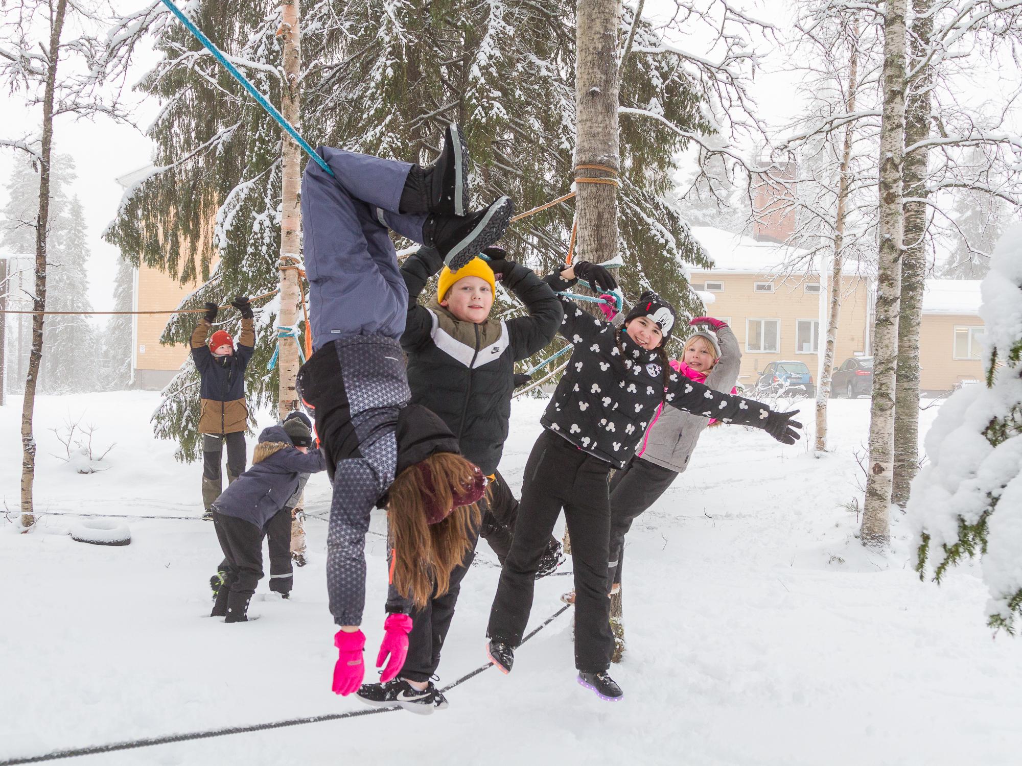 Noukavaaran koululaiset kiipeilevät iloisesti köysiradalla lumisen koulun pihametsikössä.