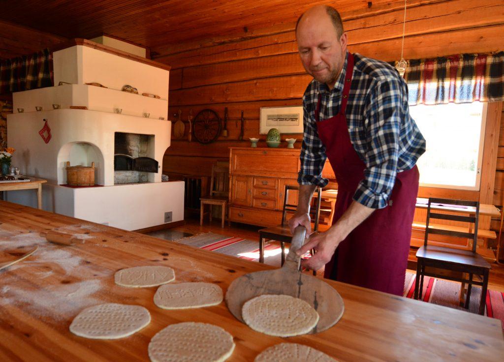 Mies nostaa leipomansa rieskan paistumaan pirtin leivinuuniin.