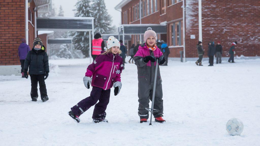 Rukan koulun oppilaat potkaisevat palloa ja hyppivät hymyillen koulun lumisella pihalla.
