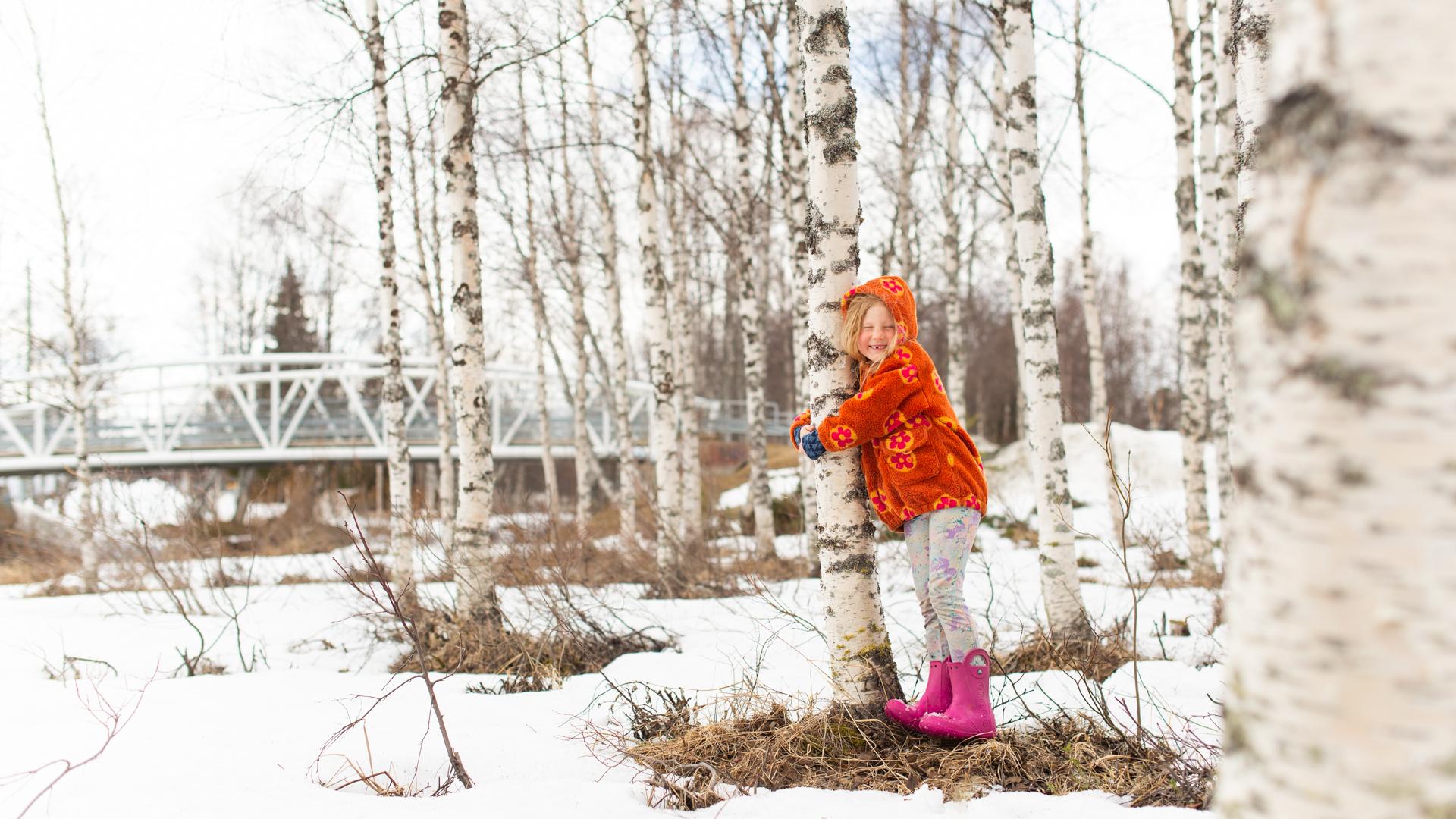 Tyttö halaa koivua lumisessa puistossa