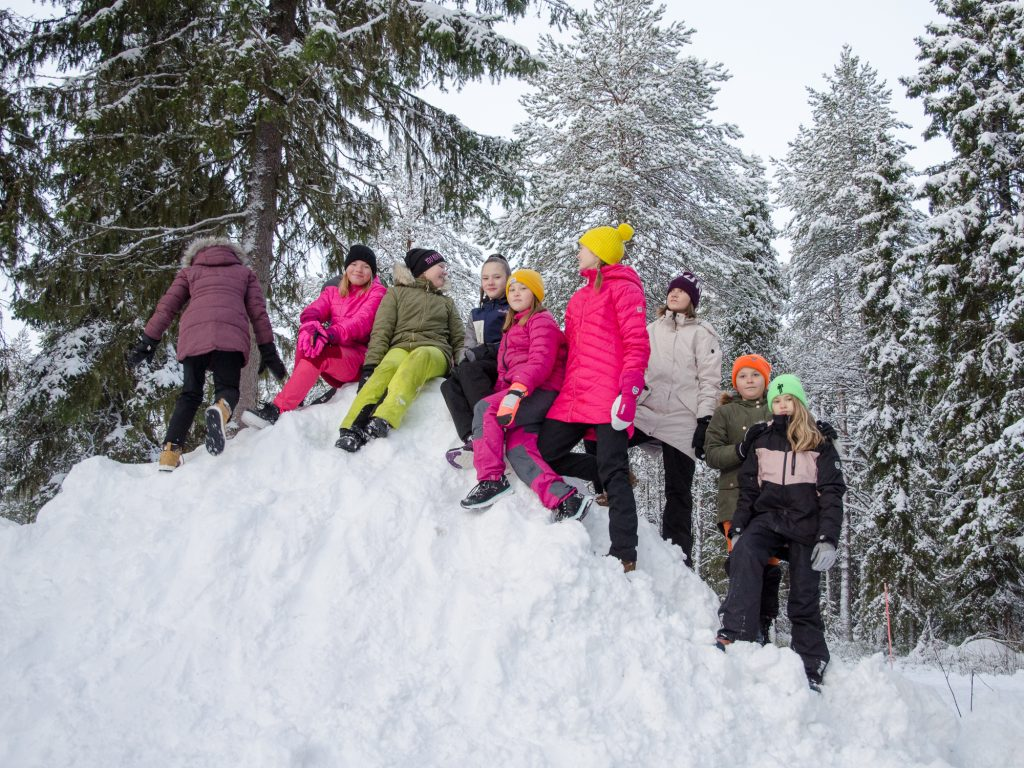 Tolpanniemen koulun oppilaita seisoo suuren lumipenkan päällä.