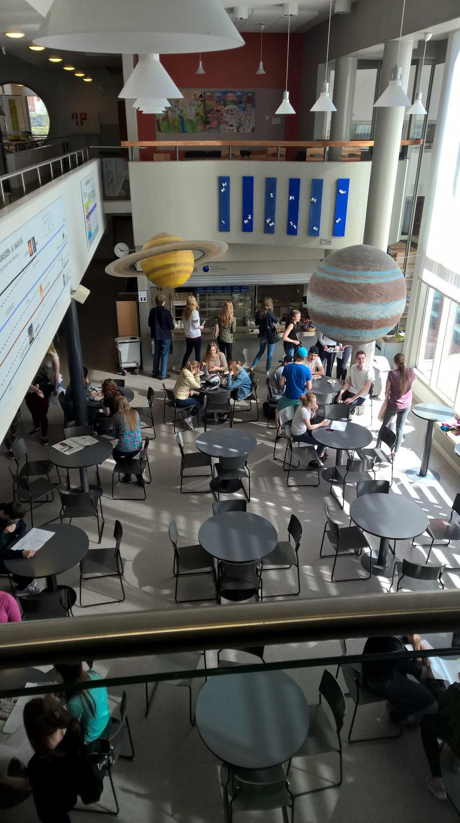 Kuusamon lukion aula on avara ja valoisa. Oppilaat opiskelevat ja nauttivat kevätauringon valosta kahvilassa.
