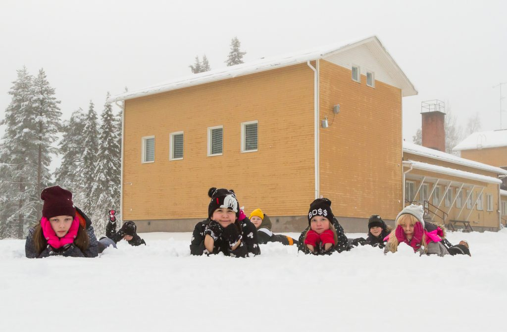 Noukavaaran koululaiset makoilevat lumessa koulun edustalla.