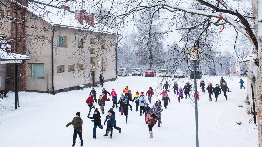 Mäkelän koululaiset kirmaavat lumisella koulupihalla.