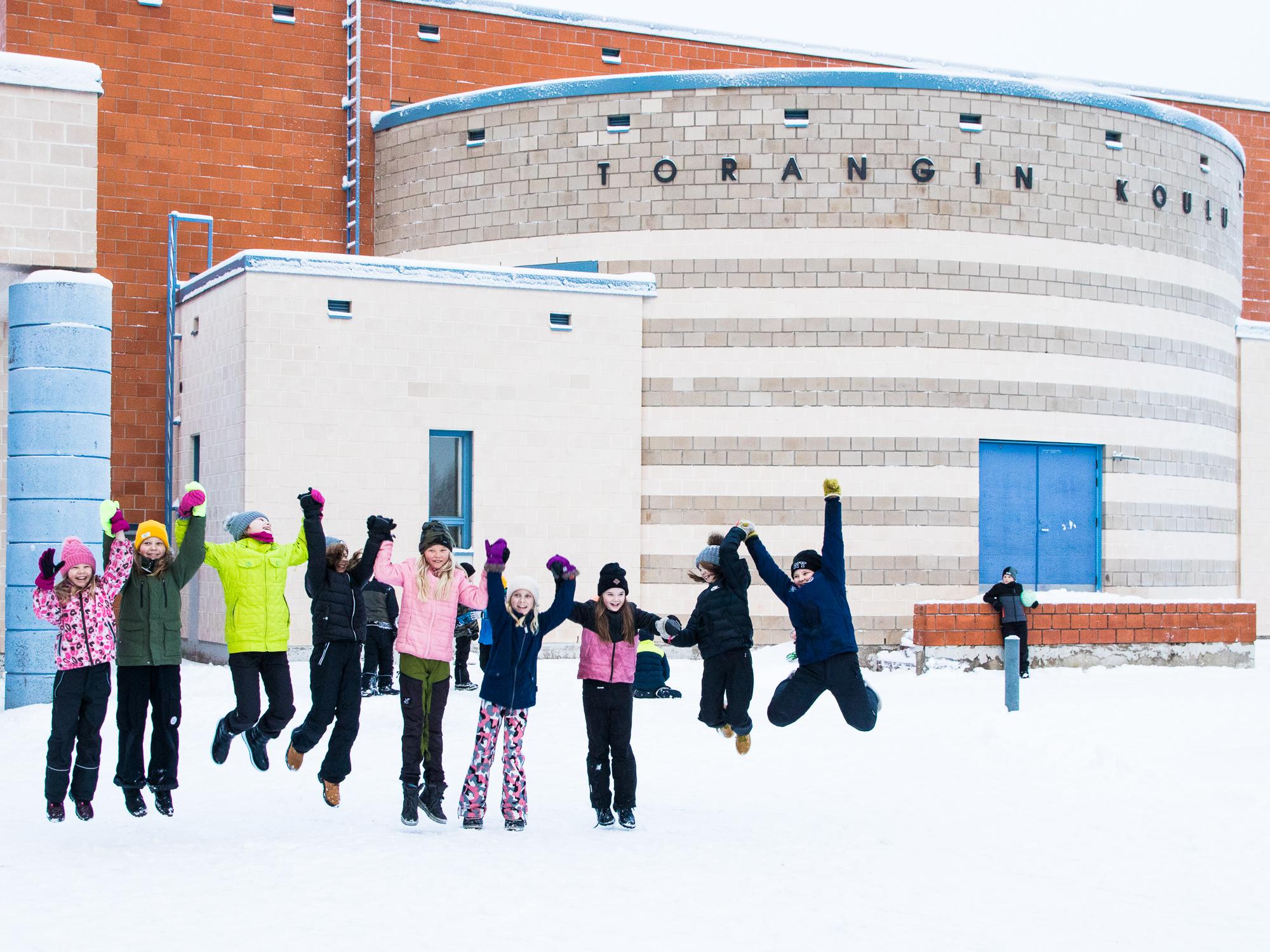Torangin koulun oppilaat hyppäävät yhdessä koulun edustalla.