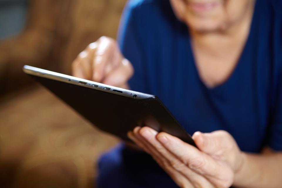 Vanhempi nainen käyttää tablettia