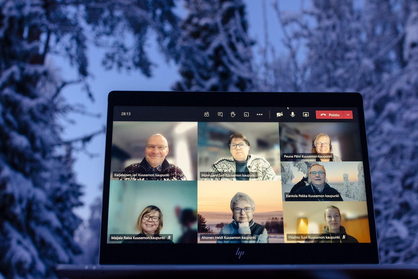 Tietokoneen näytöllä seitsemän ihmisen etäkokous. Taustalla lumiset puut ja pakkaspäivän sininen hetki.
