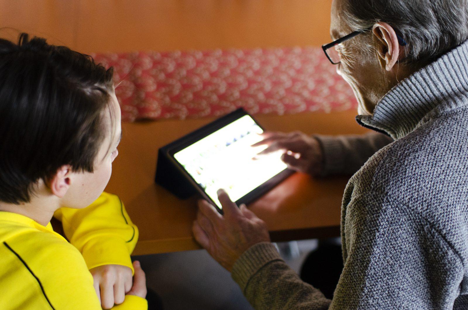 Poika ja isoisä käyttävät tablettia. Tabletti valaisee heidät.