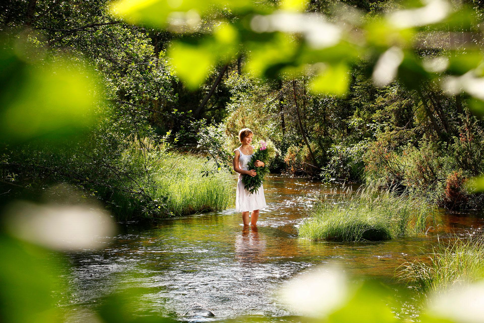 Neiti kesäheinä joella kukkakimpun kanssa