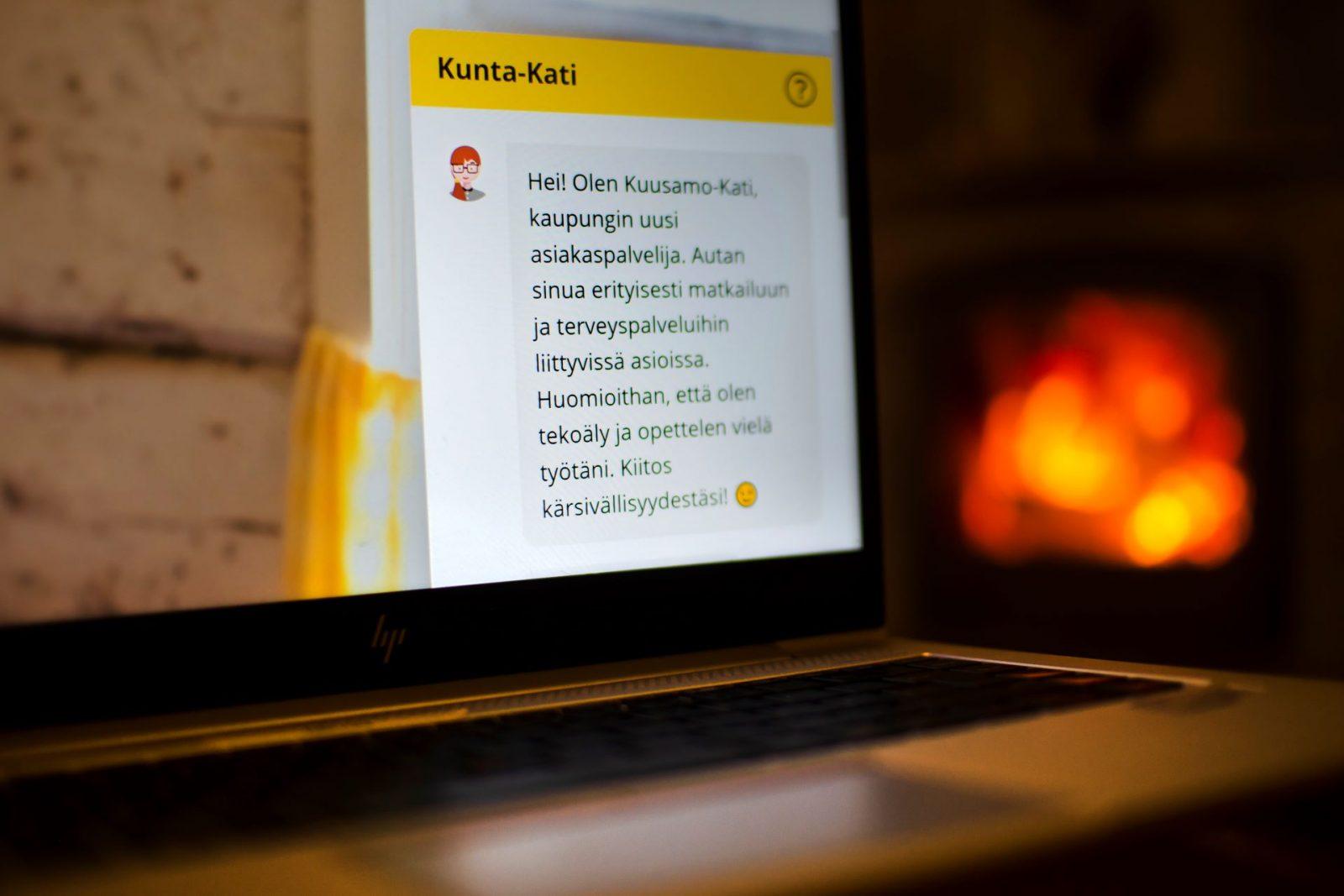 Tietokone takkataulen loisteessa. Ruudulla näkyy kirkkaana chätbotin, Kuusamo-Katin, keskusteluruutu.